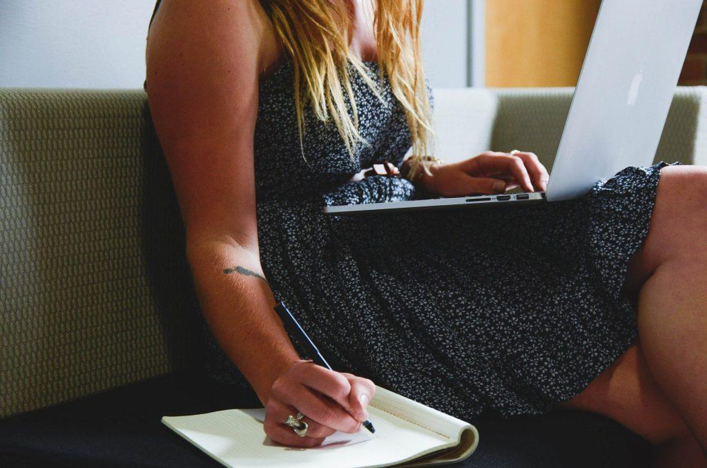 Kvinna som jobbar med laptop och block i soffa.