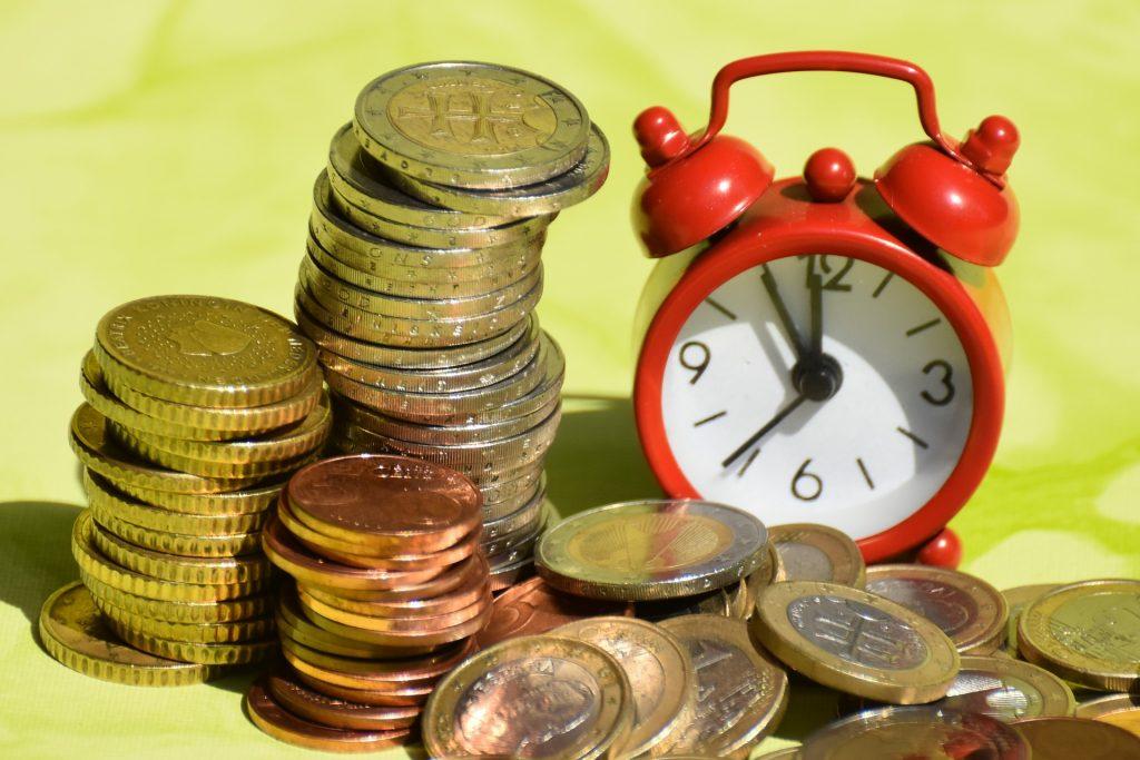 tid är pengar: Mynt och väckarklocka.